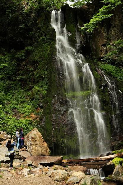 滝を見上げ、マイナスイオンを浴びる滝ガール