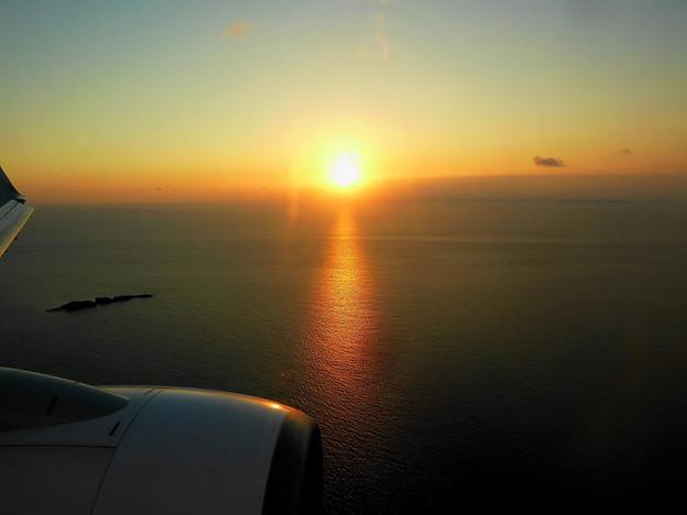 写真: 機内から見た夕陽