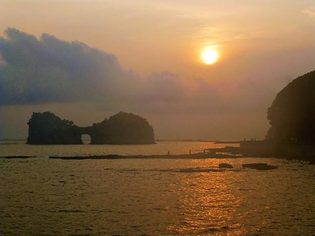 写真: 夕日の名所として知られる円月島