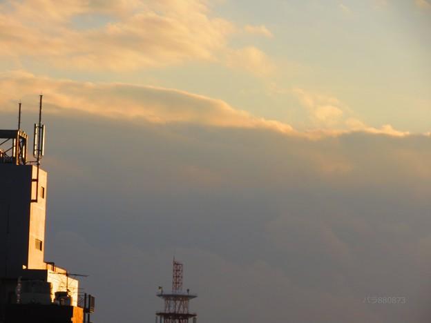 カーテンのような雨雲と鋭く光る夕焼け